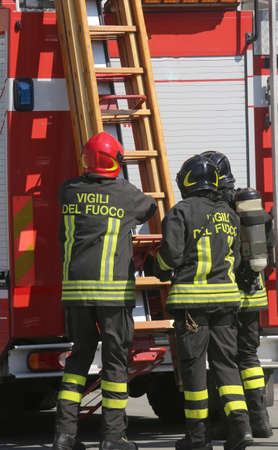 firetruck: firefighters in action take the wooden ladder from the firetruck Stock Photo