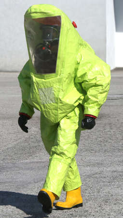 hazardous: man with yellow protective suit to manage hazardous materials