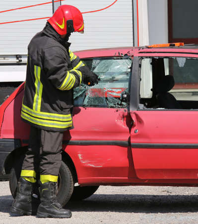 chief fireman whit red helmet while breaking the glass of a car with a special equipment