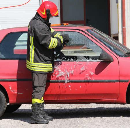 casco rojo: bombero jefe pizca casco rojo mientras que romper el cristal de un coche con un equipo especial Foto de archivo
