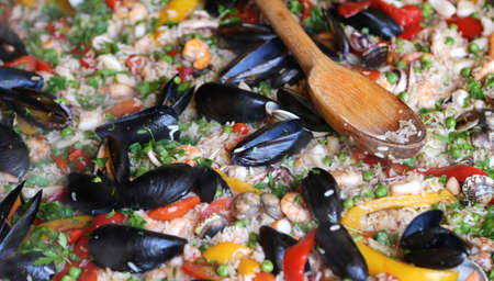 valencian: Valencian Paella rice with clams and mussels and green peas with wooden spoon
