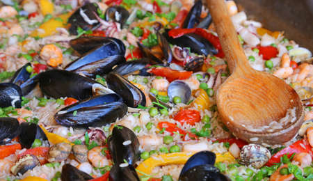 valencian: Valencian Paella rice with clams and mussels and a wooden spoon