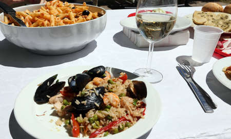 pic nic: table in the restaurant with pasta and paella rice with mussels