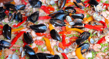 Valencian Paella rice with clams and black mussels and green peas photo