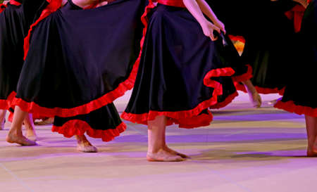 flamenco dress: legs of the dancers during the performance of flamenco dancing