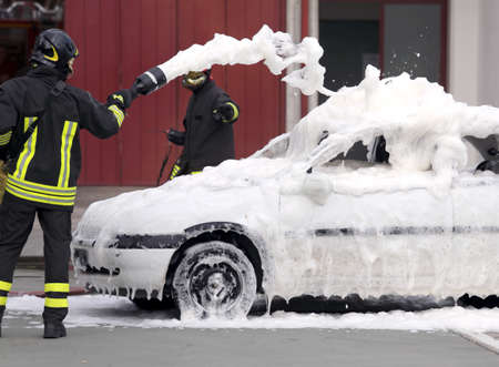 fireman with hose: firemen during exercise to extinguish a fire in a car with foam