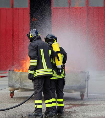 bombera: bomberos con botellas de oxígeno fuera del fuego durante un ejercicio de entrenamiento en la estación de bomberos Foto de archivo