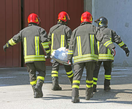 no fires: four italian firefighters carry a stretcher with injured