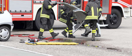 italian car: fireman in action during a road accident with car parts and the firetruck