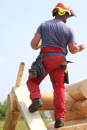 Carpenter with helmet and protective equipment to work safely on the roof of the House Stock Photo