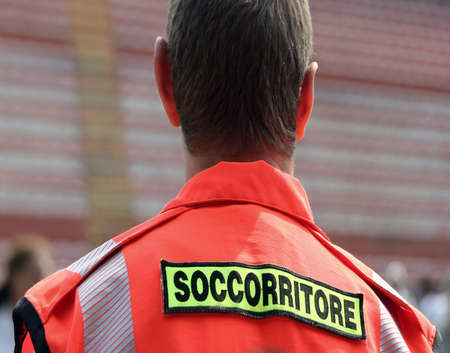 rescuer: italian rescuer with orange uniform in the stadium