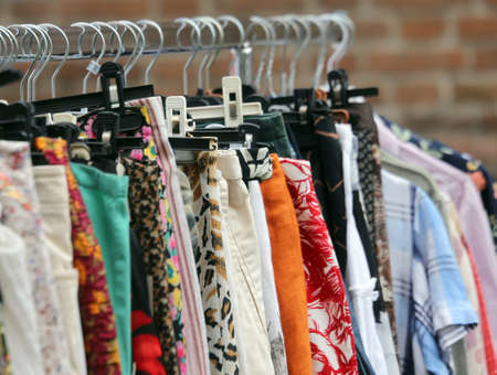 used clothes: vintage clothes hanging in the flea market of used things