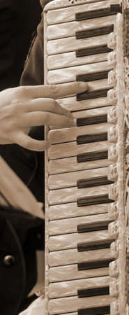 plays: hand of a woman plays the ancient accordion keyboard