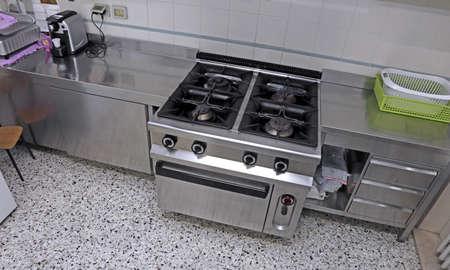 school canteen: acero cocina con estufa de acero grande para cocinar comidas a muchas personas Foto de archivo