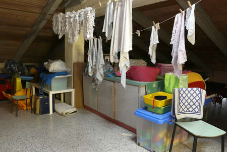 attic: Attic with many things and clothes hung out to dry Stock Photo