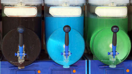 distributor: italian shave ice machine with many colored flavors at the bar Stock Photo