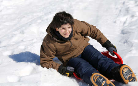 to go sledding: smiling boy enjoying sledding on snow in the mountains in winter