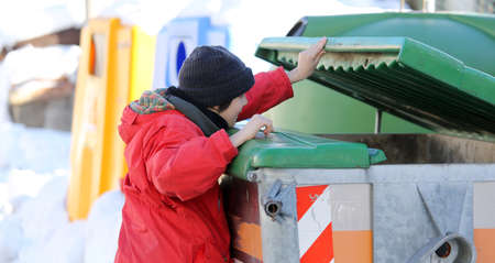 poor young boy tries to eat into the waste box in winter Banque d'images