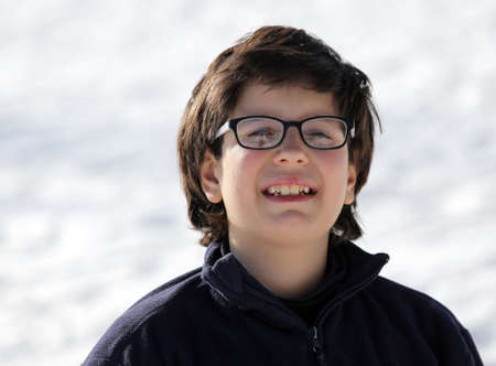 myopic: Portrait of a boy with winter clothing in the mountains in winter