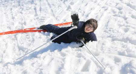 skiing accident: boy asks for help after the fall from snow skiing in the mountains in winter