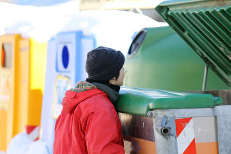 illegal immigrant: poor young boy tries to eat into the waste box in winter Stock Photo