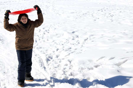 to go sledding: young boy with the Red Snow sledge in winter Stock Photo