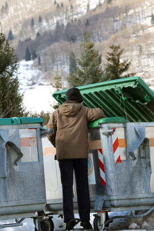 poor young boy tries to eat into the waste box in winter Stock Photo