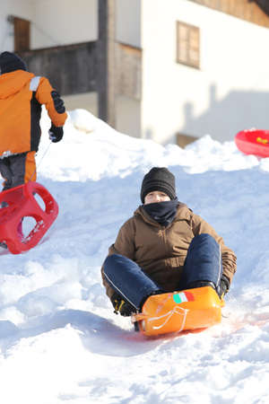to go sledding: young guy goes down with the orange bob by descent on the ski slope in the mountains in winter