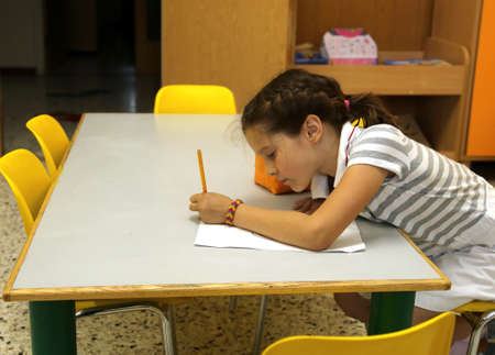 pretty little girl: pretty little girl writes on the paper in school sitting on Chair