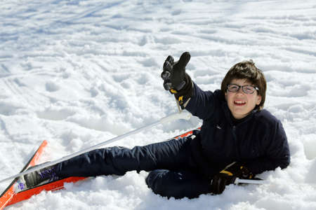 skiing accident: young boy asks for help after the fall with skis Stock Photo