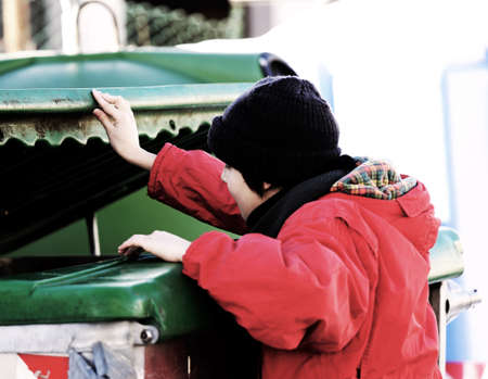 marginalized: poor young boy tries to eat into the waste box in winter Stock Photo