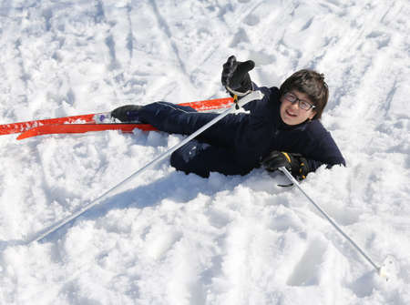 skiing accident: young boy asks for help after the fall from snow skiing in the mountains in winter