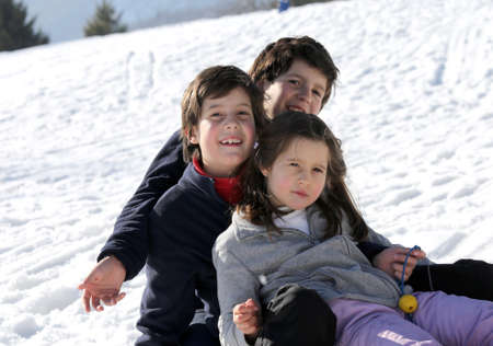 kinship: three smiling siblings over the sled in winter in the mountains with snow