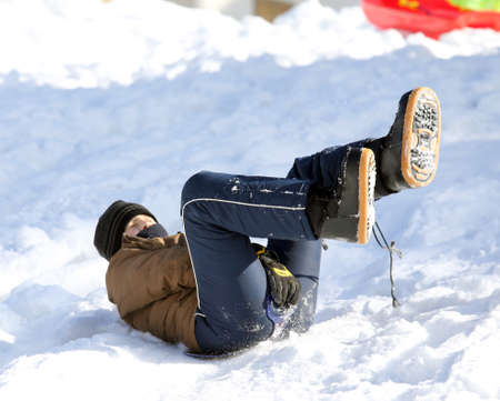 to go sledding: boy enjoying sledding on snow in the mountains in winter