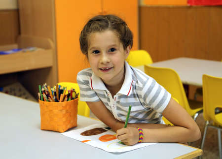 smiling little girl while drawing with the pencil colours at school