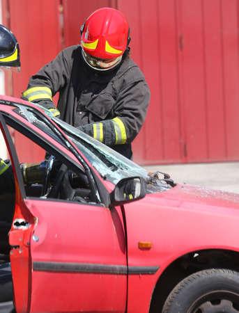 casco rojo: bombero jefe pizca casco rojo mientras que romper el parabrisas de un coche después de accidente de tráfico Foto de archivo