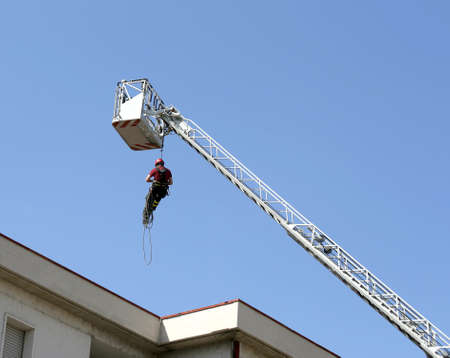rappel: brave firefighter down with the rope in the building during a fire alarm in the firehouse Stock Photo