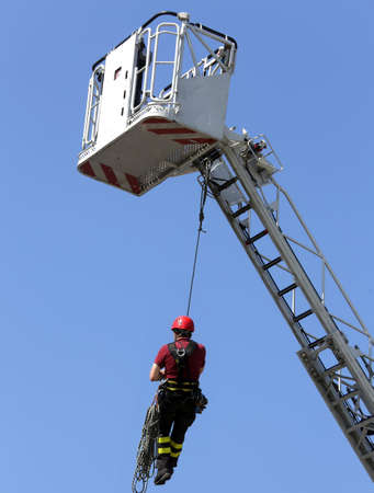 rappel: firefighter hung the rope climbing during the practical exercise in firehouse Stock Photo