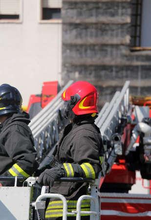 voiture de pompiers: pompier dans la cage du moteur de feu avec casque rouge Banque d'images