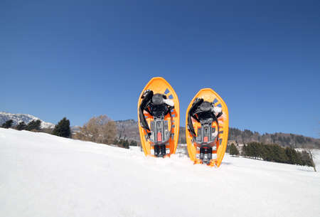 snowshoes: two orange snowshoes in mountains in winter