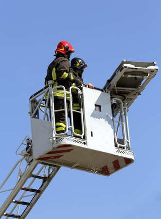 voiture de pompiers: deux pompiers dans la cage élevée du moteur de feu Banque d'images