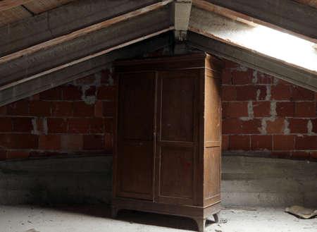 onbewoond: oude houten kast in de stoffige zolder van het onbewoonde huis