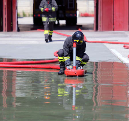rescuer: Firefighter positions a powerful fire hydrant during the exercises in the Fire Hall Stock Photo