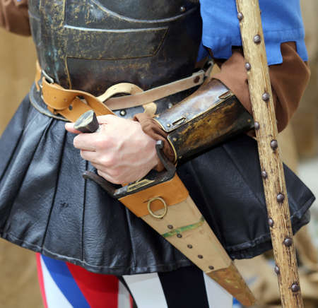 middle ages: medieval soldier with his hand on the sheath knife during a combat reenactment of the middle ages