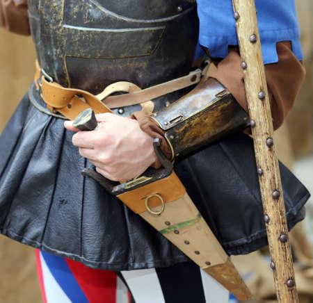medioevo: soldato medievale con la sua mano sul coltello fodero durante un combattimento rievocazione del medioevo