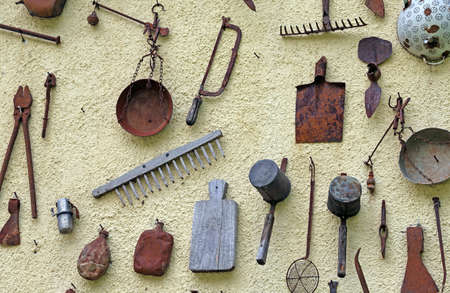 long  ago: many rusted farming tools hanging on the wall of the rural House