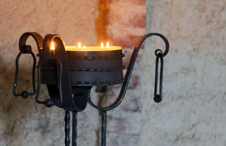 candlelit: ancient iron candelabrum to illuminate the Interior of the medieval castle