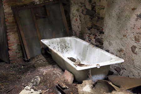 bathtub old: dirty old bathtub in unsafe House destroyed and abandoned Stock Photo