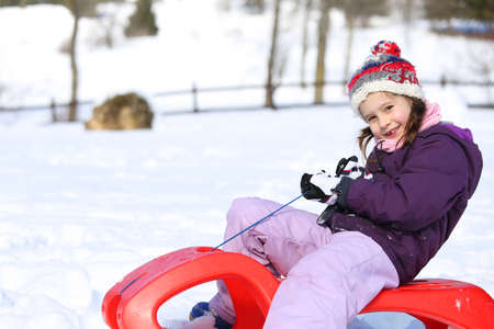 enjoyed: pretty enjoyed girl plays with bob in the mountains in the snow Stock Photo
