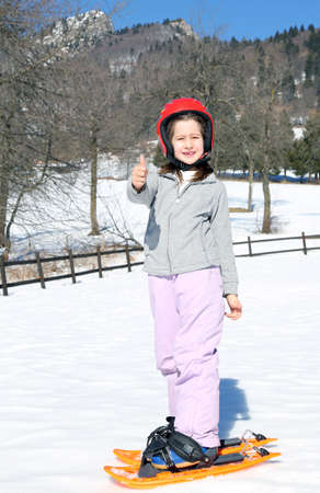 snowshoes: young girl with orange snowshoes on snow in winter